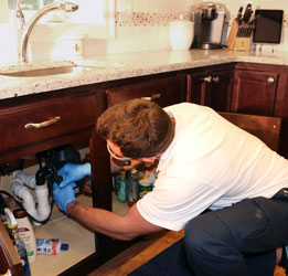 one of our plumbers is performing a maintenance check on a garbage disposal