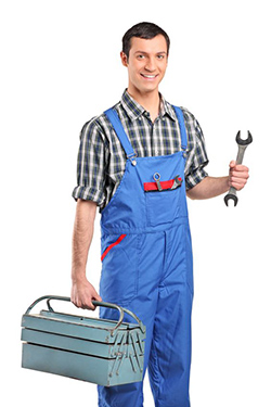 John holding a wrench in one hand and in the other his plumbing tool box